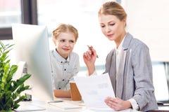 Generi il lavoro con il computer ed i documenti mentre figlia che la considera nell'ufficio di affari immagini stock
