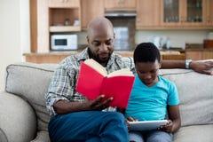 Generi il libro di lettura mentre il figlio che si siede accanto lui facendo uso della compressa digitale fotografie stock libere da diritti