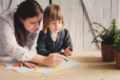 Generi il ragazzo d'istruzione del bambino per disegnare con le matite a casa Fotografie Stock
