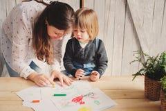 Generi il ragazzo d'istruzione del bambino per disegnare con le matite a casa Fotografia Stock