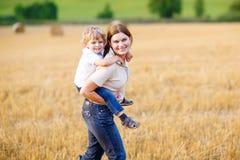 Generi il ragazzo del bambino della tenuta sulle armi sul giacimento di grano di estate fotografie stock