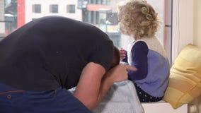 Generi il solletico la sua ragazza della figlia che si siede vicino alla finestra Caduta della bufera di neve della neve video d archivio