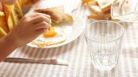 Generi il succo d'arancia di versamento il suo piccolo figlio durante la prima colazione delle uova fritte di mattina archivi video