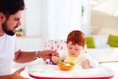 Generi insegna al figlio, bambino a tenere il cucchiaio ed a mangiare dai suoi propri Fotografia Stock Libera da Diritti