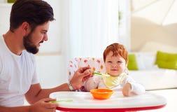 Generi insegna al figlio, bambino a tenere il cucchiaio ed a mangiare dai suoi propri Fotografia Stock