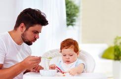 Generi insegna al figlio, bambino a tenere il cucchiaio ed a mangiare dai suoi propri Immagini Stock Libere da Diritti