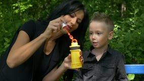 Generi intrattenere e l'insegnamento del suo ragazzo che fa le bolle di sapone iridescenti su un banco stock footage