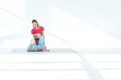 Generi l'aiuto con l'allungamento dell'esercizio alla piccola figlia Fotografia Stock Libera da Diritti