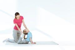 Generi l'aiuto con l'allungamento dell'esercizio alla piccola figlia Immagine Stock