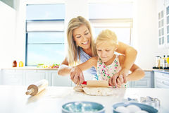Generi l'aiuto di sua figlia sveglia rotolare la pasticceria Fotografia Stock