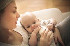 Generi l'alimentazione del suo bambino piccolo con latte a casa immagine stock