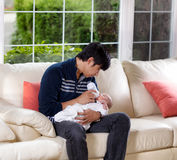Generi l'alimentazione di suo figlio infantile sul sofà bianco Immagini Stock