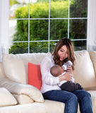 Generi l'alimentazione di suo figlio infantile sul sofà bianco Fotografia Stock Libera da Diritti