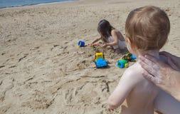 Generi l'applicazione della crema del sole al suo bambino mentre il suo gioco della figlia sopra Immagine Stock