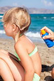 Generi l'applicazione della protezione solare al suo bambino ad una spiaggia Fotografia Stock Libera da Diritti