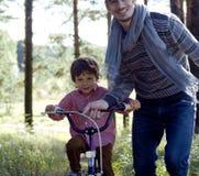 Generi l'apprendimento di suo figlio per guidare sulla bicicletta fuori Immagine Stock