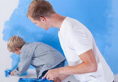Generi l'esame di suo figlio durante la pittura della parete Immagine Stock Libera da Diritti