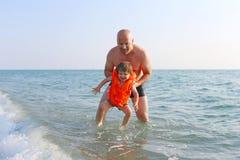 Generi l'insegnamento dei suoi 2 anni di figlio per nuotare in mare fotografia stock