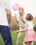 Generi l'un l'altro la palla di lancio della figlia e della madre nel parco Immagine Stock Libera da Diritti