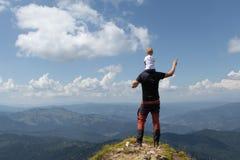 Generi la bambina della tenuta sulla sua spalla mentre sopra la montagna Giorno di estate pieno di sole fotografia stock