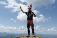 Generi la bambina della tenuta sulla sua spalla mentre sopra la montagna Giorno di estate pieno di sole fotografie stock