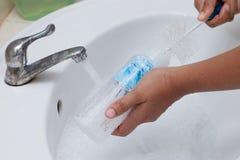 Generi la bottiglia per il latte del bambino di lavaggio della mano sul lavandino bianco immagine stock libera da diritti