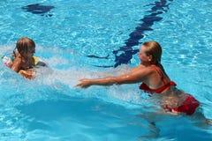 Generi la cattura di sua figlia che salta nella piscina Feste felici fotografia stock