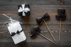 Generi la celebrazione del giorno o di compleanno del ` s con i biscotti del segno del presente, dello smoking, dei baffi e del c Fotografia Stock Libera da Diritti