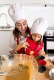 Generi la cottura con la piccola figlia in grembiule e cucini i muffin della muffa del materiale da otturazione del cappello con  Fotografia Stock