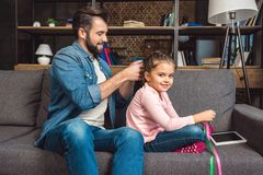 generi la fabbricazione della treccia dei capelli per la figlia mentre si siedono sullo strato immagine stock libera da diritti