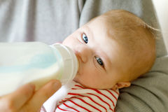 Generi la figlia d'alimentazione del neonato con latte in bottiglia di professione d'infermiera Fotografie Stock Libere da Diritti