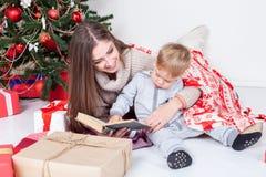 Generi la lettura del libro ad un bambino al nuovo anno di Natale Immagine Stock Libera da Diritti
