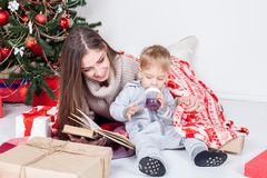 Generi la lettura del libro ad un bambino al nuovo anno di Natale Fotografia Stock