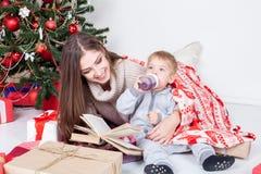Generi la lettura del libro ad un bambino al nuovo anno di Natale Immagini Stock Libere da Diritti