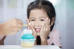 Generi la mano che accende la candela sul bigné di compleanno per il bambino Fotografia Stock