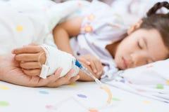 Generi la mano che tiene la mano malata della figlia che ha soluzione IV fotografia stock libera da diritti
