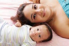 Generi la menzogne con il suo bambino sul letto Immagine Stock