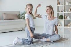 generi la mostra del muscolo del bicipite a sua figlia colpita fotografia stock libera da diritti
