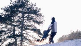 Generi la rotazione di suo figlio che giudica le sue mani al rallentatore in foresta innevata all'inverno all'aperto archivi video