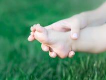 Generi la tenuta dei piedi del neonato sul fondo dell'erba verde Il concetto di tenerezza, preoccuparsi e di salute materne fotografia stock libera da diritti