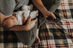 Generi la tenuta del suo bambino mentre per mezzo del suo telefono immagine stock libera da diritti