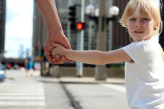 Generi la tenuta della mano del bambino della figlia dietro i semafori Fotografie Stock Libere da Diritti