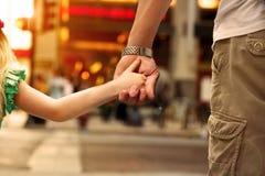 Generi la tenuta della mano del bambino della figlia dietro i semafori Fotografia Stock