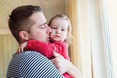 Generi la tenuta di sua figlia piccola nelle sue armi Fotografia Stock Libera da Diritti