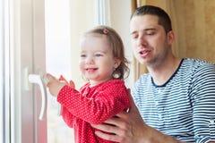 Generi la tenuta di sua figlia piccola, stante alla finestra Immagini Stock Libere da Diritti