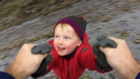 Generi la tenuta di suo figlio dalla mano e la circonduzione intorno stock footage
