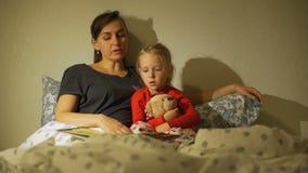 Generi le favole della lettura al suo bambino nella sera stock footage