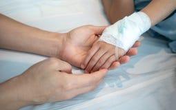 Generi le mani che tengono la sua mano paziente del bambino con il intraveno salino immagini stock libere da diritti