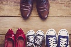 Generi le scarpe del ` s disposte davanti alle scarpe del ` s della madre con il bambino sul wo Immagini Stock