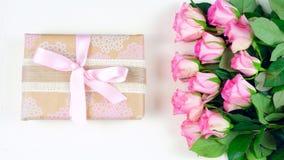 Generi le spese generali del giorno del ` s con il regalo e le rose rosa sul fondo di legno bianco della tavola Fotografia Stock